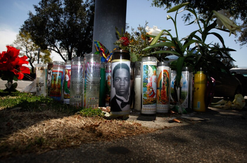 Candles, flowers, and a photo taped to a candle make up a memorial at the street corner where Kendrec McDade, 19, was fatally shot by two Pasadena police officers in March 2012.