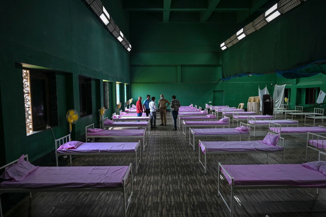 People stand among rows of cots.