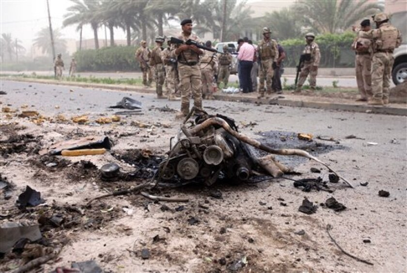 Iraqi soldiers secure the site of a car bomb in Baghdad, Iraq, Monday, June 7, 2010. Iraqi officials say a car bomb has exploded in a shopping area in western Baghdad, killing three people. (AP Photo/Karim Kadim)