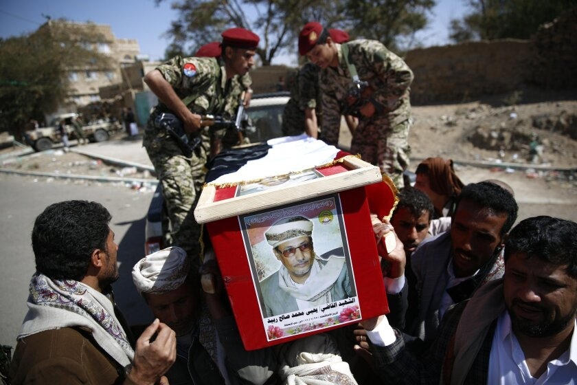 Shiite fighters, known as Houthis, and other people carry the coffin of judge Yahya Rubaid, who was killed with his family by a Saudi-led airstrike in Sanaa, Yemen, Tuesday, Jan. 26, 2016. (AP Photo/Hani Mohammed)