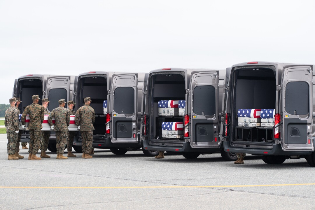 A case with the remains of a fallen service member is placed inside a transfer vehicle at Dover Air Force Base.