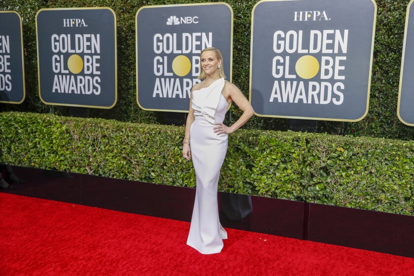 Reese Witherspoon arriving at the 2020 Golden Globe Awards red carpet in a white ruffled gown.