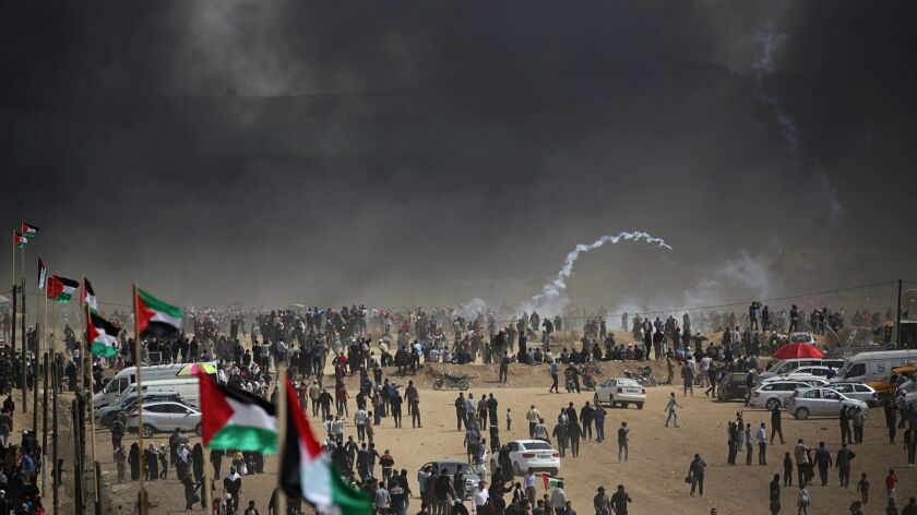 Black smoke from burning tires hovers over Palestinian protesters during clashes with Israeli troops near the border.