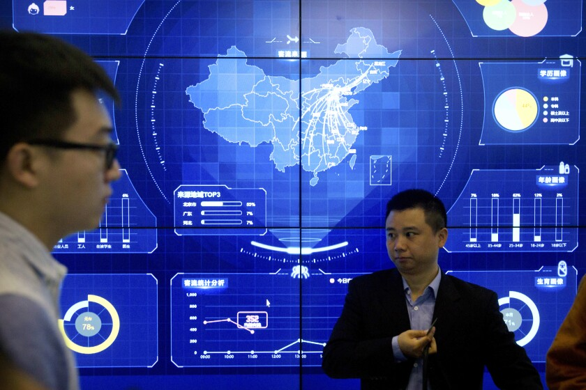 """In this April 26, 2018, file photo, visitors stand in front of an electronic data display showing a map of China at the Global Mobile Internet conference in Beijing. China's industry ministry has announced a 6-month campaign to clean up what it says are serious problems with internet apps violating consumer rights, cyber security and """"disturbing market order."""" (AP Photo/Mark Schiefelbein, File)"""