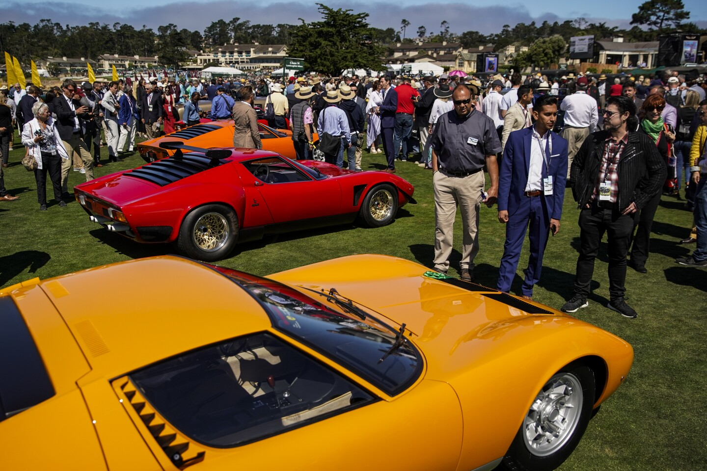 PEBBLE BEACH, CALIF. - AUGUST 18: Concours d'Elegance attendees walk among the cars in the Class N, Lamborghini Miura cars at the 69th Pebble Beach Concours d'Elegance at the Pebble Beach golf course on Sunday, Aug. 18, 2019 in Pebble Beach, Calif. (Kent Nishimura / Los Angeles Times)