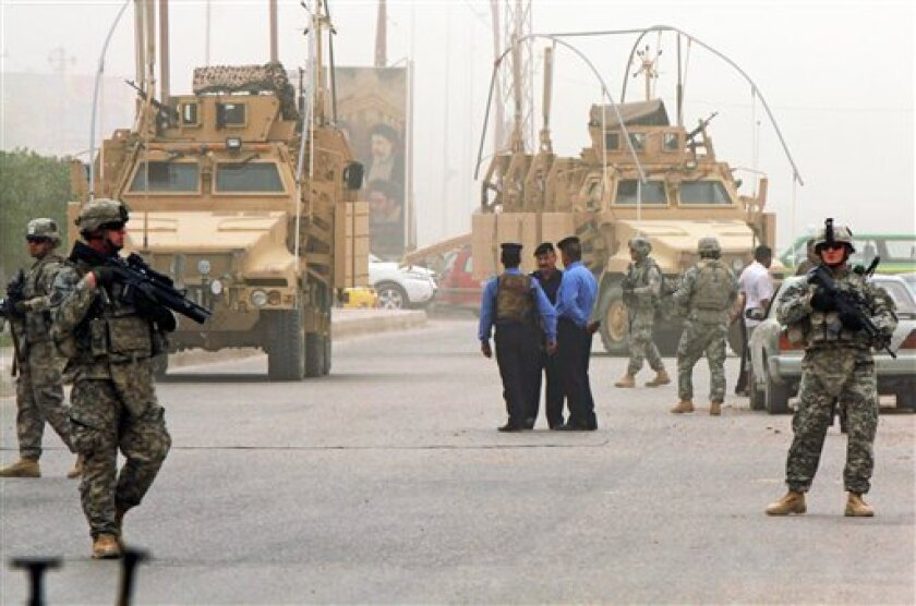 U.S. Army soldiers and Iraqi security forces stand guard at the scene of a roadside bomb attack that exploded in Najaf, 160 kilometers (100 miles) south of Baghdad, Iraq Sunday, April 3, 2011. (AP Photo/Alaa al-Marjani)