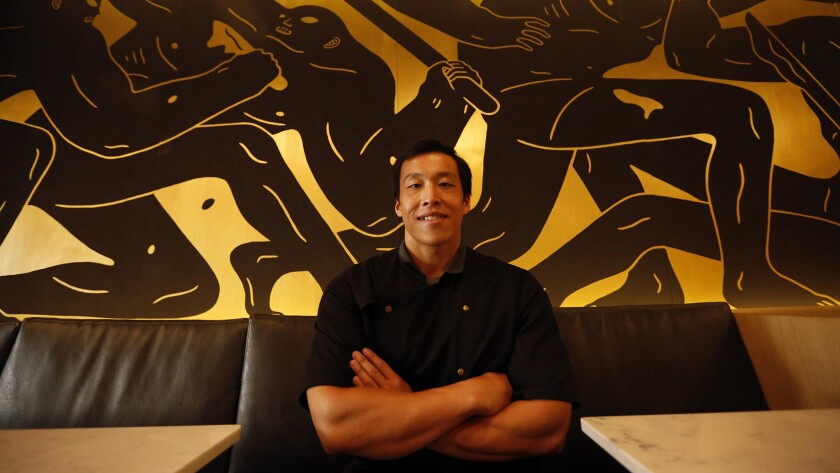 Chef Erwin Tjahyadi sits in front of a mural by artist Cleon Peterson that anchors the main dining r