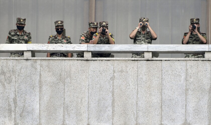 FILE - In this Sept. 16, 2020, file photo, North Korean army soldiers wearing face masks look at the South side during South Korean Unification Minister Lee In-young's visit to Panmunjom in the Demilitarized Zone, South Korea. North Korea is further toughening its restriction on the entry to sea as part of elevated steps to fight the coronavirus pandemic, state media said Sunday, Nov. 29, two days after South Korea said the North even banned fishing at sea. (Park Tae-hyun/Korea Pool via AP, File)