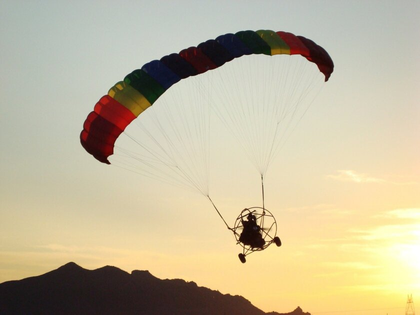 This April 5, 2009 photo provided by Arizona Powerchutes shows pilot Randy Long parachuting on a sunset flight over the Sonoran Desert in Peoria, Ariz. Picture a dune buggy with a massive parachute attached to the back of it, sort of a cross between something the Wright Brothers might have designed and that flying machine from the Mad Max movies. A powerchute provides a flying experience unlike any other. (AP Photo/Arizona Powerchutes)