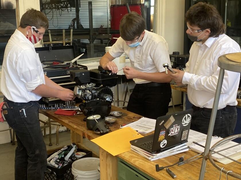 Small Engines Team members Jasper Dilts, Robert Wilson and Garrett Pekelder participate in a Small Engine tear down contest.