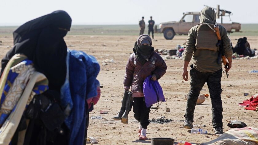 Civilians fleeing fighting between Syrian Democratic Forces and Islamic State in the Syrian village of Baghuz wait to be screened and registered by the U.S.-backed SDF in Deir Ezzor province on Sunday.