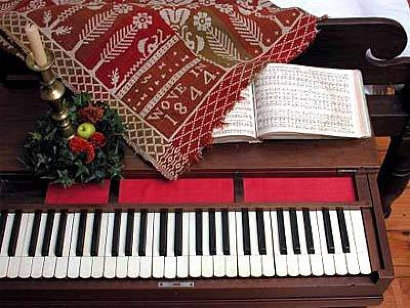 A candle, greenery, an 1844 coverlet and a hymnal opened to a Christmas song help decorate a room at Belair Mansion.