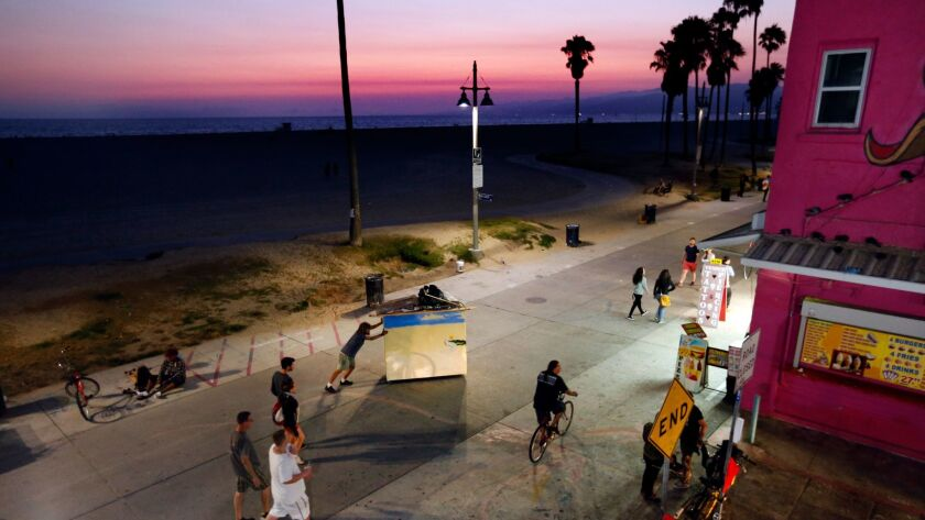 Chris Buck wheels his portable home, which has a bed inside, along the boardwalk in Venice Beach.