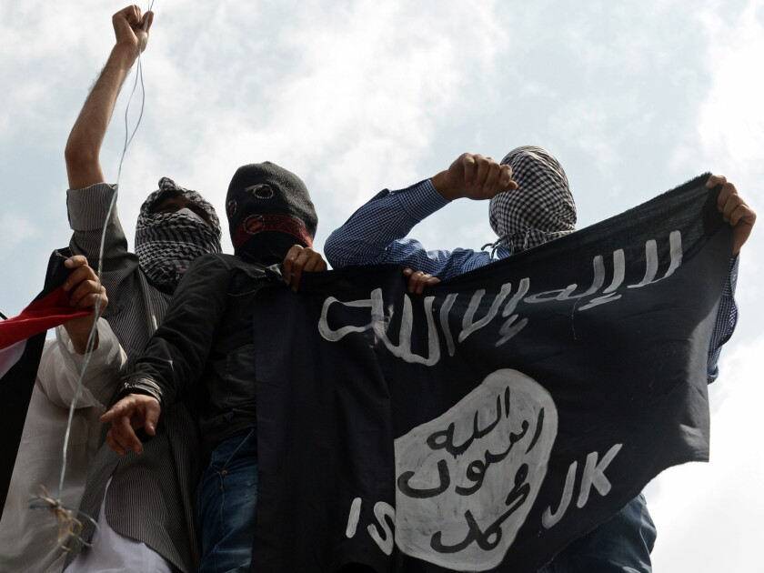 """Demonstrators in the disputed Kashmir region hold up an Islamic State flag during a demonstration July 18, 2014. Al Qaeda says it is launching a new branch to """"wage jihad"""" in South Asia."""