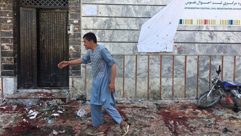 An Afghan man walks outside a voter registration center, which was attacked by a suicide bomber in