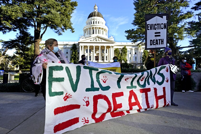 Demonstrators hold signs against evictions in front of the Capitol in Sacramento