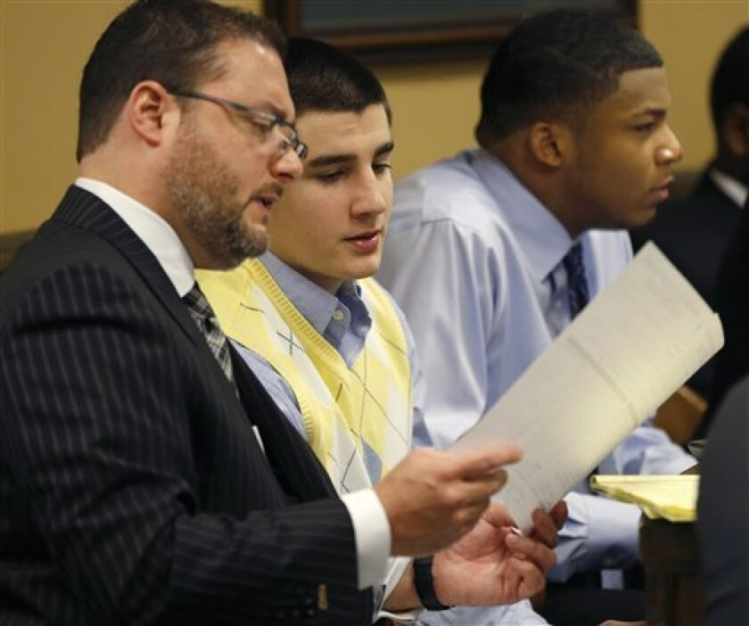 From left, Defense attorney Adam Nemann, his client, looks over evidence with defendant Trent Mays, 17, center, and defendant 16-year-old Ma'lik Richmond during Mays and Richmond's trial on rape charges in juvenile court on Thursday, March 14, 2013 in Steubenville, Ohio. Mays and Richmond are accused of raping a 16-year-old West Virginia girl in August of 2012. (AP Photo/Keith Srakocic, Pool)