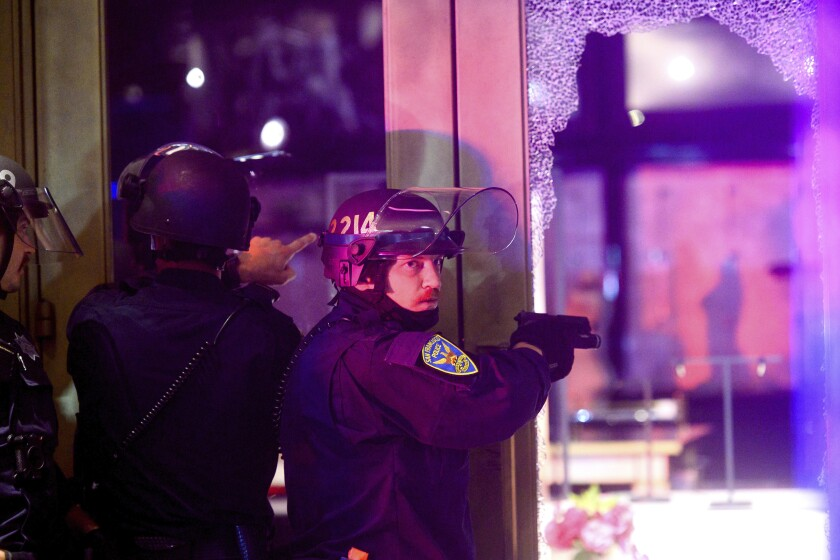 A police officer aims his weapon while clearing a vandalized Victoria's Secret store in San Francisco on Saturday.