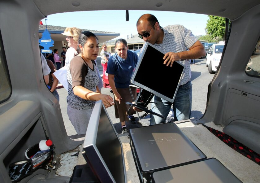Volunteer Aditya Shah (right) helps Yolanda Perez place computers in the back of her SUV during a computer distribution last week at Rose Elementary School.