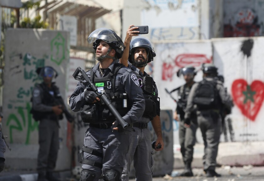 An Israeli border policeman takes a selfie during clashes in the West Bank city of Bethlehem, Friday, July 21, 2017. Israel police severely restricted Muslim access to a contested shrine in Jerusalem's Old City on Friday to prevent protests over the installation of metal detectors at the holy site.