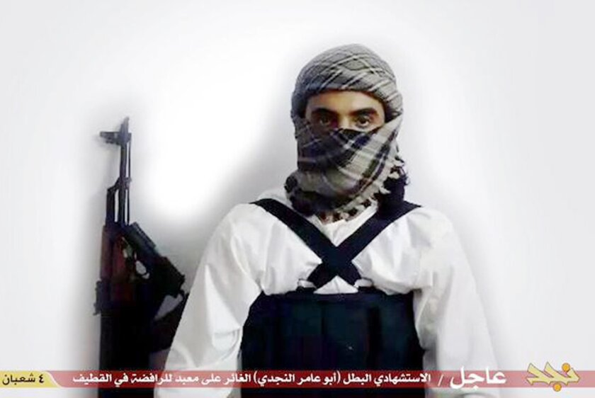 """This image taken from a militant website associated with Islamic State extremists, posted May 23, 2015, purports to show a suicide bomber, with the Arabic bar below reading: """"Urgent: The heroic martyr Abu Amer al-Najdi, the attacker of the (Shiite) temple in Qatif"""", which the Islamic State group's radio station claimed responsibility for."""