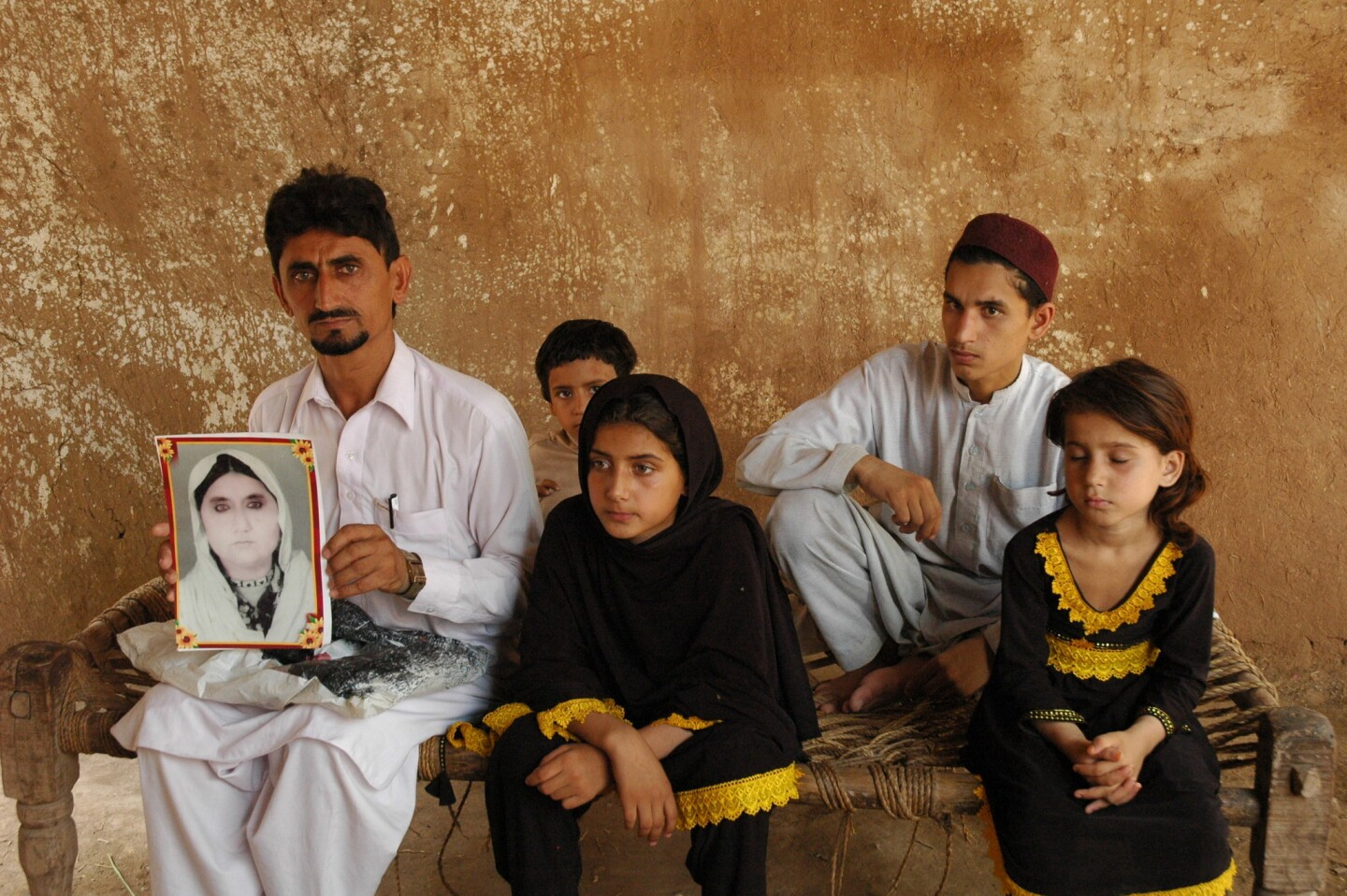 """Rafeequl Rehman sits with his children, holding a photograph of his mother, Mamana Bibi, who he says was killed in a U.S. drone strike in Pakistan last year. """"If I get some money I will get a lawyer and fight for my right to get justice from the world,"""" Rehman told Amnesty International. """"I am waiting for my justice."""""""