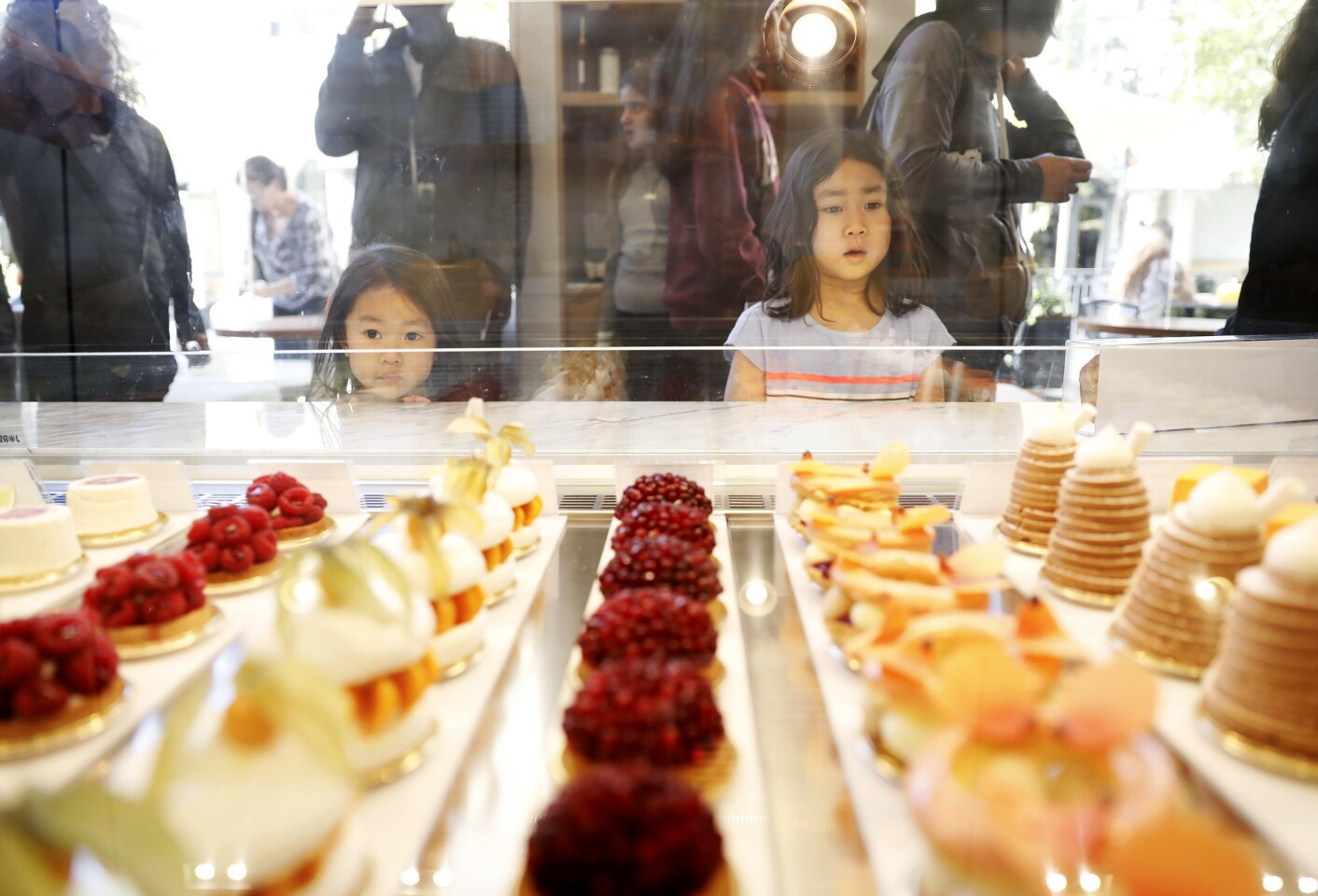 Three-year-old Lydia Sebata, left, and her sister Candice, 5, right, peer into the glass case at Dominique Ansel Bakery at the Grove in Los Angeles.