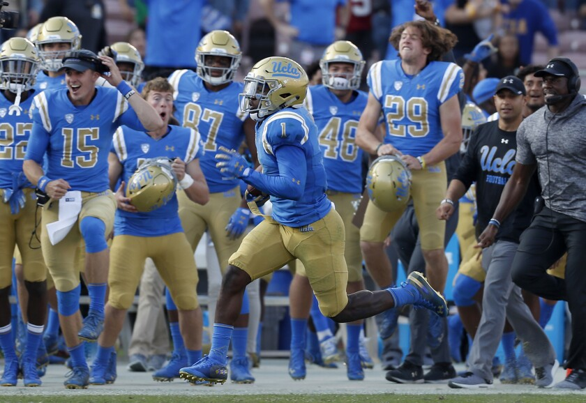 UCLA's Darnay Holmes returns a Stanford kickoff for a touchdown during the third.
