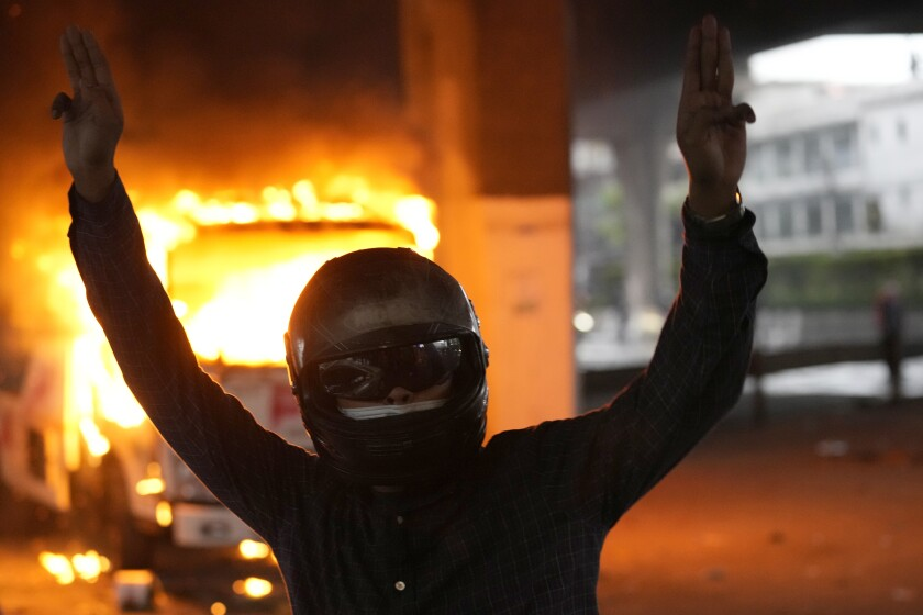 Anti-government protester display the three-finger symbol of resistance in front of burning police truck during protest in Bangkok, Thailand, Wednesday, Aug. 11, 2021. Protesters demanded the resignation of Prime Minister Prayuth Chan-ocha for what they say is his failure in handling the COVID-19 pandemic. (AP Photo/Sakchai Lalit)