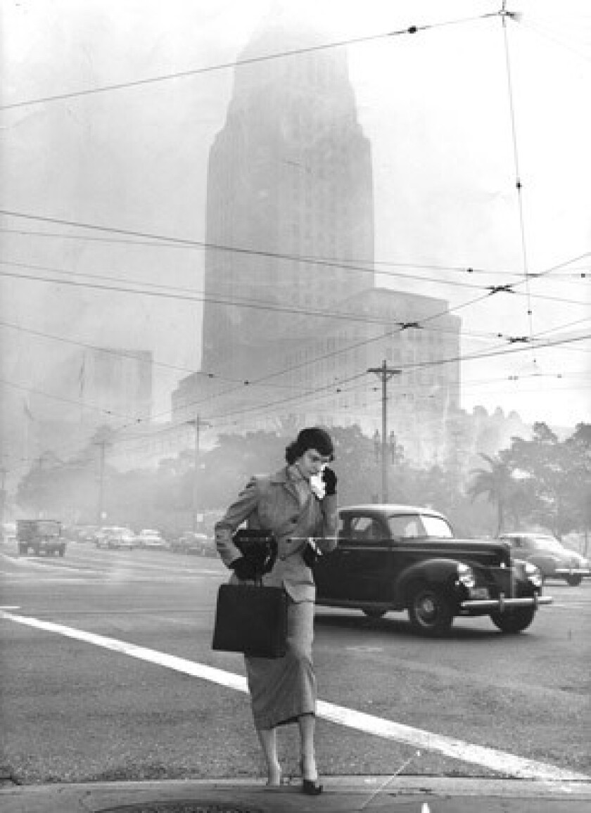 The smog near L.A. City Hall is so bad in 1953 that pedestrians carry rags to wipe tears.