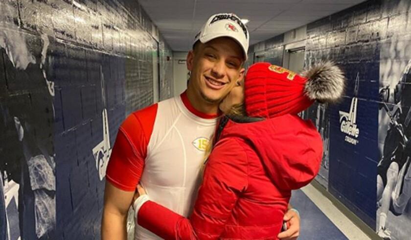 Brittany Matthews kisses Kansas City Chiefs quarterback Patrick Mahomes in a Gillette Stadium hallway.