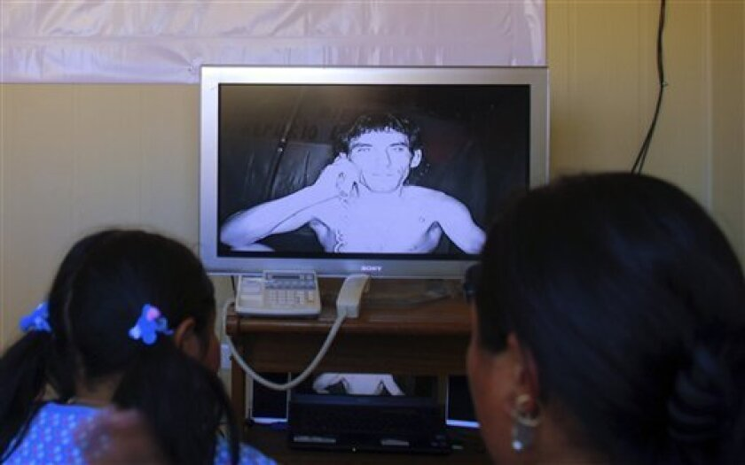 In this photos provided by Chile's government, trapped miner Claudio Yanez talks to his relatives during a video conference at the collapsed San Jose mine in Copiapo, Chile, Saturday, Sept. 4, 2010. Thirty-three miners have been trapped deep underground in the copper and gold mine since it collapsed on Aug. 5. (AP Photo/Chile's government)