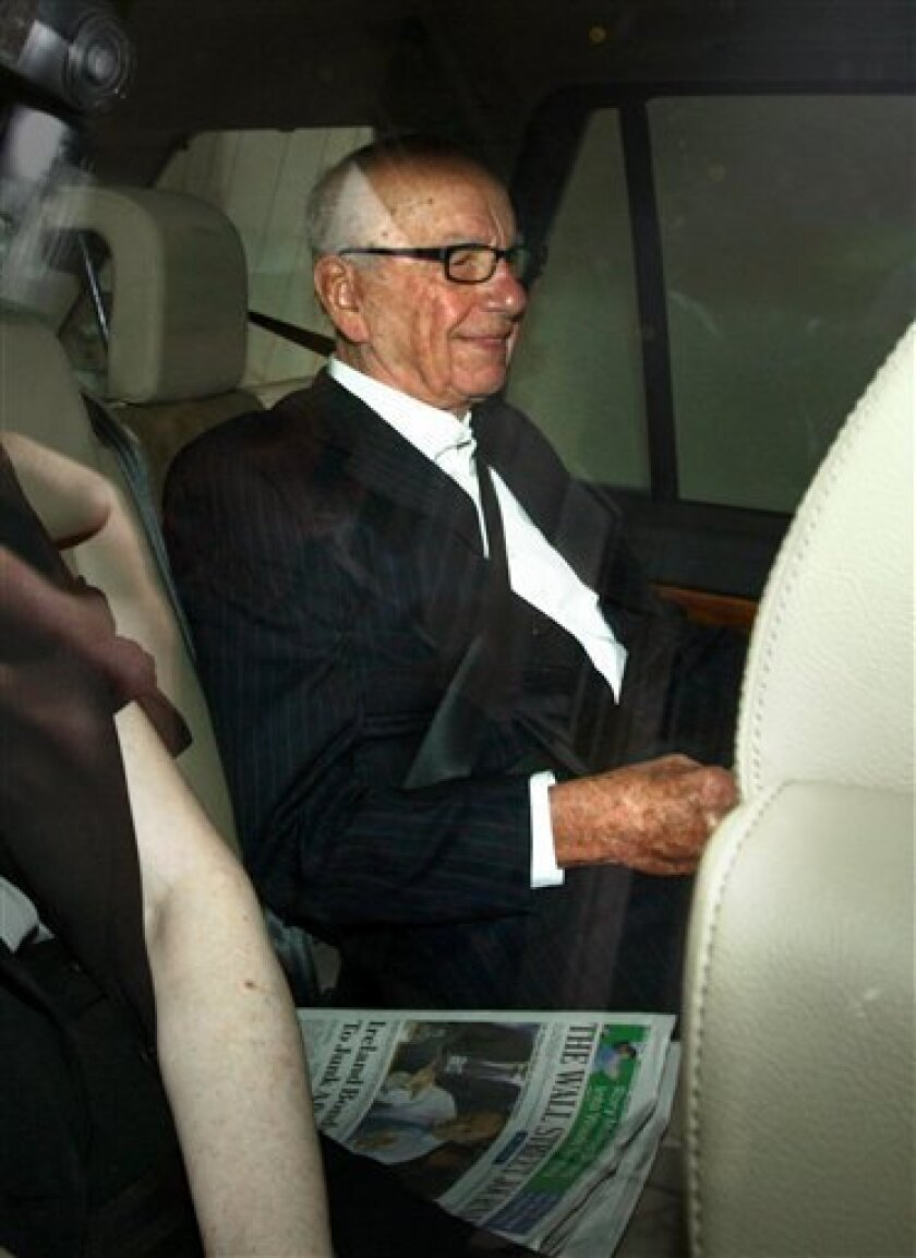 Rupert Murdoch leaves his home in Mayfair, London, as British Prime Minister David Cameron joined demands for the media mogul to drop his BSkyB takeover bid in the wake of the phone-hacking scandal Wednesday July 13, 2011. Britain's House of Commons is poised to demand that Rupert Murdoch give up on his ambition of taking over a lucrative broadcaster while a phone hacking scandal rages around his British newspaper holdings. Cameron has put his party's weight behind an opposition motion up for a vote Wednesday which declares that bidding for full control of British Sky Broadcasting would not be in the national interest. (AP Photo/Steve Parsons) UNITED KINGDOM OUT NO SALES NO ARCHIVE