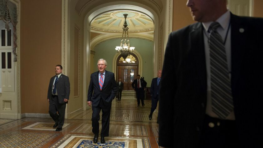 Senate Majority Leader Mitch McConnell, of Ky., center, walks with his security team from the Senate