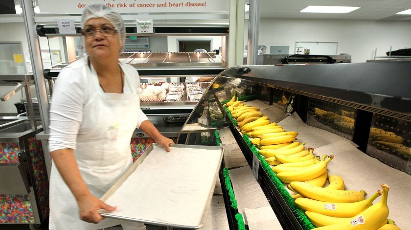 Linda Gomez stocks bananas for lunch at Bravo Medical Magnet High School. The health benefits of cafeteria workers and other L.A. school employees are preserved under a new three-year agreement.