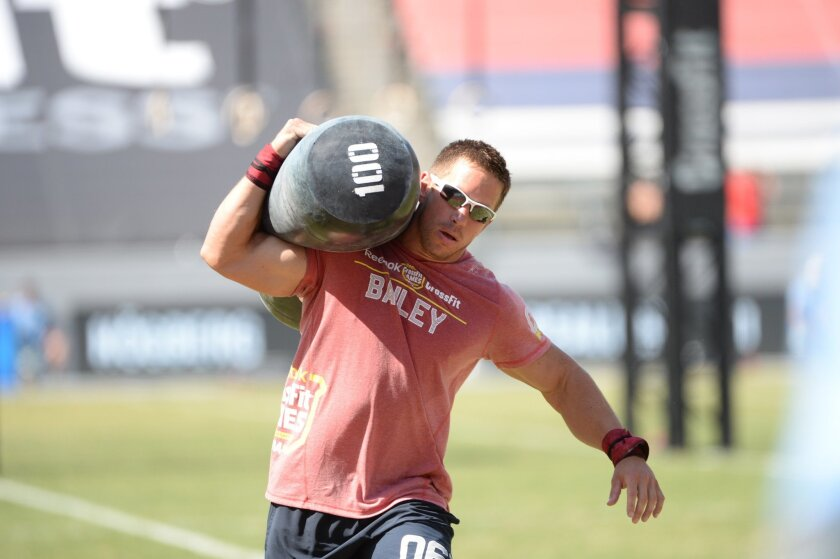 San Diegan Dan Bailey carries a 100-pound bag in a race during a CrossFit competition.