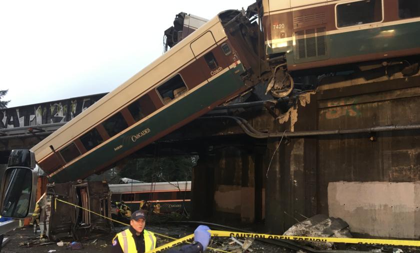 Un vagón de tren del servicio Amtrak cuelga tras descarrilarse...