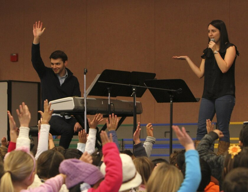 Peter Dugan raises his hand as his girlfriend, Kara Sainz, asks a group of Barnett Elementary school students if they know what a composer is during a performance at the school. Dugan and Sainz both attend Julliard Music School, and Kara's sisters attend Barnett Elementary school.