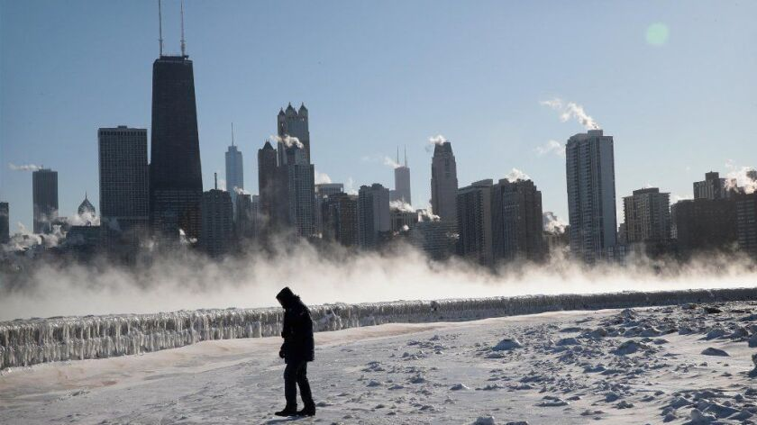 A man walks along Lake Michigan as temperatures in Chicago hover around 20 degrees below zero on Jan. 30.