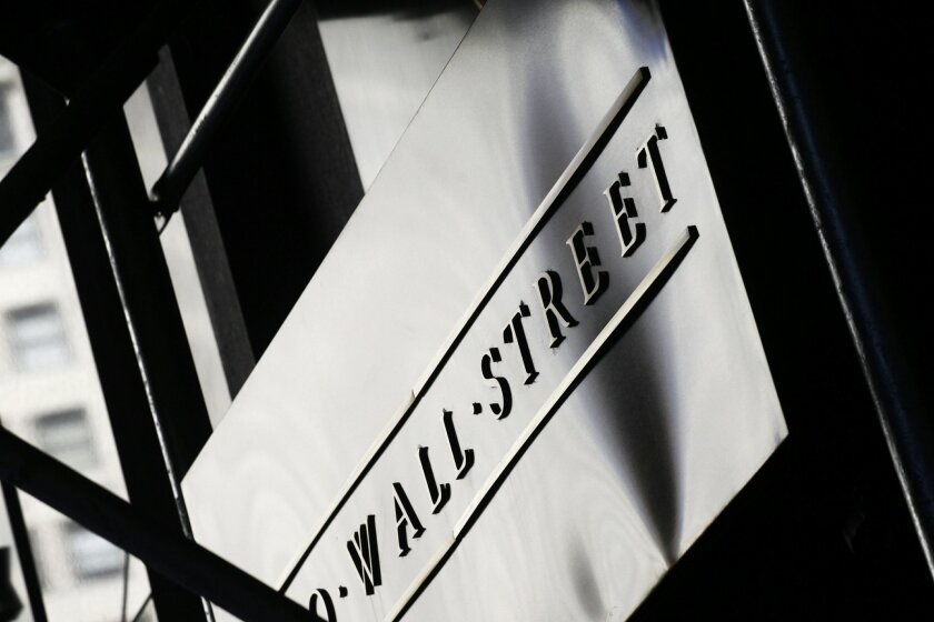 FILE - This July 15, 2013, file photo, shows a sign for Wall Street outside the New York Stock Exchange. Global markets shuddered again Thursday, Feb. 11, 2016, with bank stocks in particular getting hammered, oil falling further and investors turning to perceived safe havens like gold. (AP Photo/M