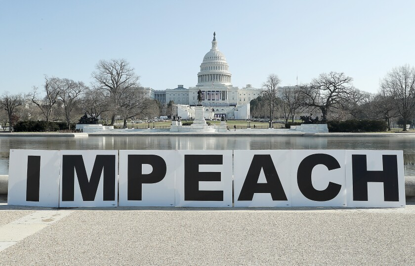 People gather at the base of the U.S. Capitol with large IMPEACH and REMOVE letters on January 12, 2021 in Washington, DC.