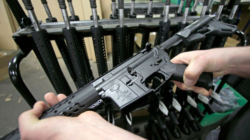 FILE - In this April 10, 2013 file photo, craftsman Veetek Witkowski holds a newly assembled AR-15 r