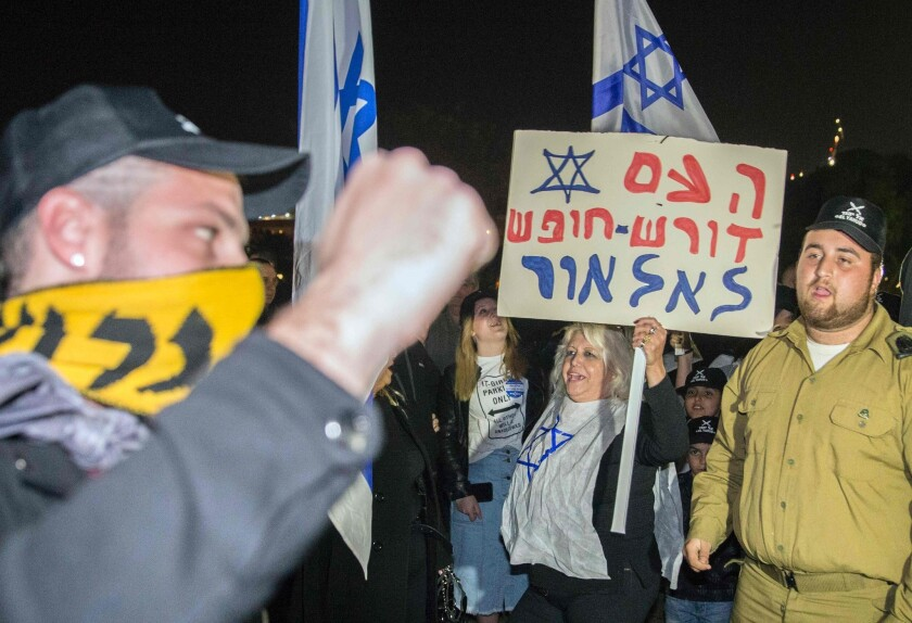 """An Israeli citizen holds a banner reading in Hebrew: """"Fighters, the people are with you"""" during a demonstration in Tel Aviv on Thursday to support an Israeli soldier who was suspended after being caught on video shooting a wounded Palestinian assailant in the head as he lay on the ground."""