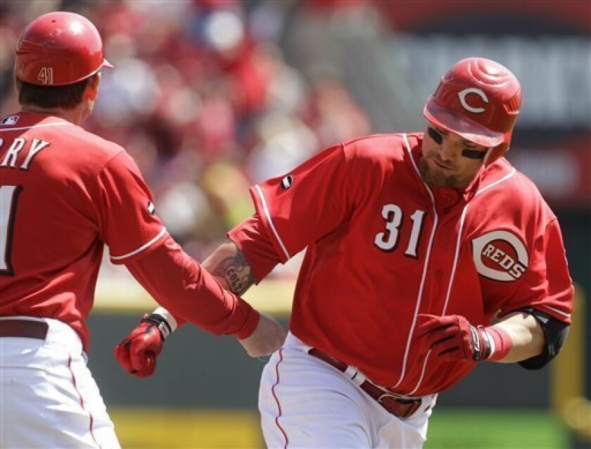 Cincinnati Reds left fielder Jonny Gomes (31) is congratulated by third base coach Mark Berry after hitting a solo home run off Milwaukee Brewers starting pitcher Randy Wolf in the second inning of a major league baseball game on Sunday, April 3, 2011, in Cincinnati. (AP Photo/Al Behrman)