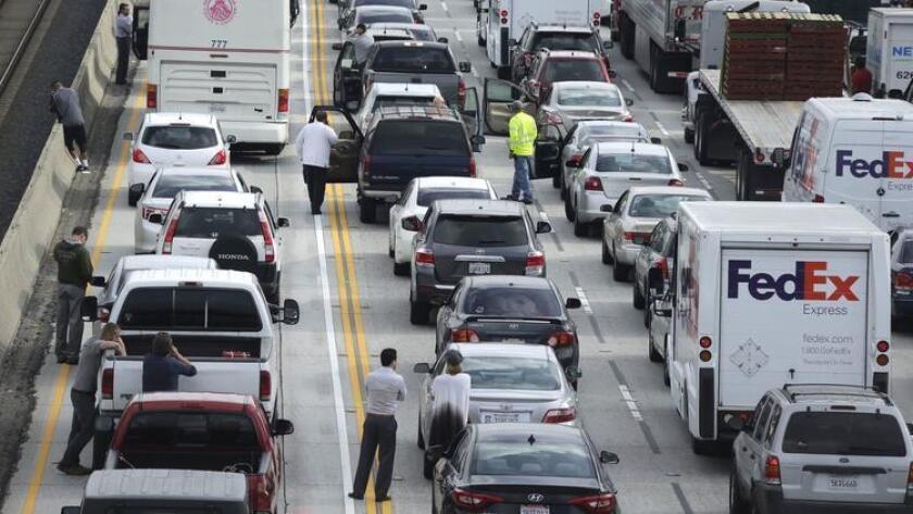 Conductores esperan afuera de sus vehículos, mientras las autoridades investigan el objetivo que apareció entre los carriles de la autopista 2010.