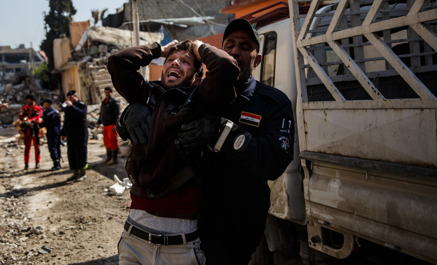 A man overcome with grief cries out as he is escorted away after finding a loved one dead amid the rubble of a destroyed home following an airstrike in Mosul, Iraq.