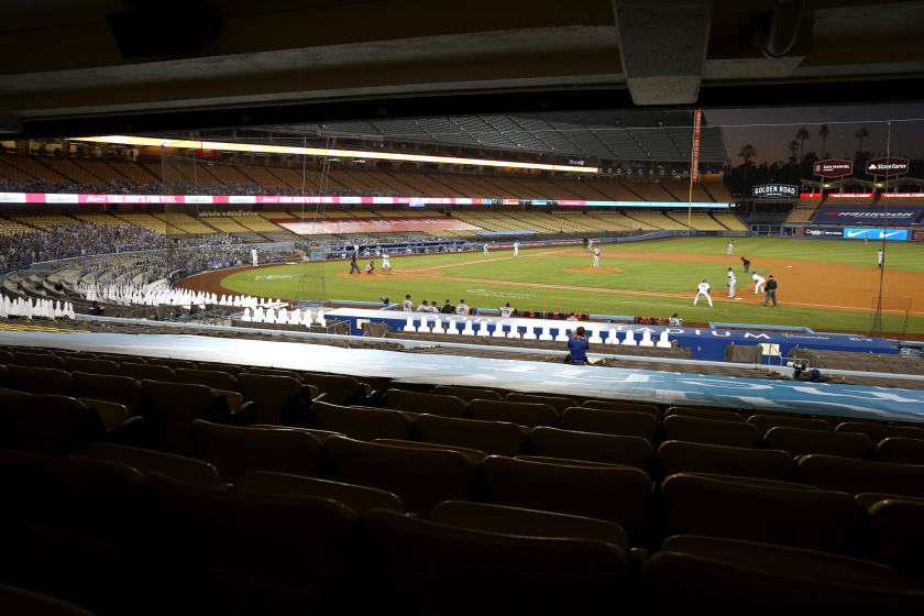 A view of a game being played at Dodger Stadium with cardboard cutouts in some seats.