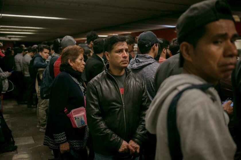 Víctor Cruz Ortega (centro) espera el tren durante su viaje matutino en la Ciudad de México. Cruz fue deportado de California hace dos meses y dejó atrás a toda su familia, incluyendo a su esposa e hijos (Meghan Dhaliwal / para The Times).