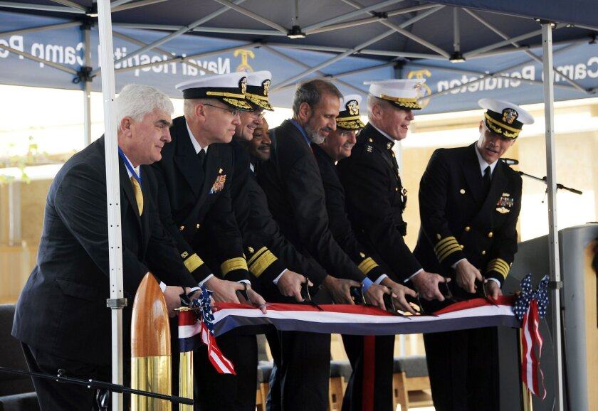 The official party cuts a slice of the ribbon during the ceremony to formally open Naval Hospital Camp Pendleton.  (From left to right) Richard Heim, president and CEO western region, Clark Construction Group; Commander, Naval Facilities Engineering Command Atlantic Rear Adm. Douglas G. Morton; Dep