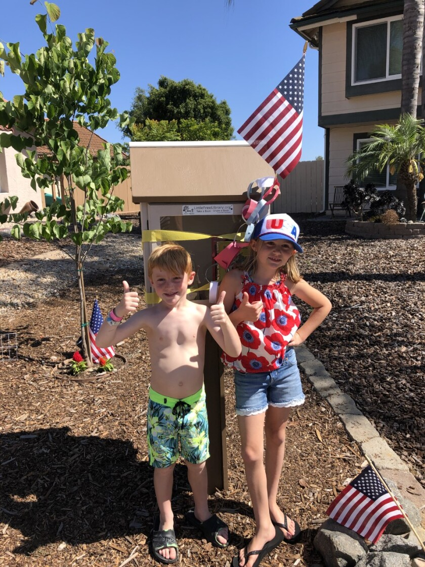 """Two siblings used their savings to open a small neighborhood 'library' in memory of their brother Jack. Violette, age 7, and Hudson, age 5, Marsolais cashed in the $205 in their savings account that they were going to use to buy an XBOX and instead bought supplies to build a 'Little Free Library.' The nonprofit 'Little Free Library organization fosters neighborhood book exchanges to bring the community together and to share a love of reading. The Marsolais 'Little Free Library' is among than 90,000 throughout the country and around the world. Violette and Hudson planted """"memory trees"""" with heart shaped leaves in honor of their brother, who was still born, near the book-exchange box in their front yard on W. Knapp Drive. """"It's my desire to see the community come together and share love here,"""" said their mother Kari Marsolais. From left, Hudson and Violette Marsolais at a ribbon cutting the family held for the library with neighbors and friends earlier this summer."""